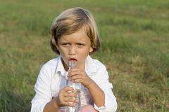 Young boy drinking water outdoors Royalty Free Stock Image