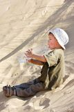 Young boy drinking water in sand Stock Photos