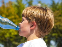 Young boy drinks water out of a bottle. After sports Stock Photo