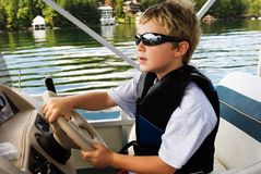 Young Boy driving a boat. Young boy at the wheel of a boat learning to drive, with the shoreline in the distance stock photos