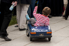 Young boy driving police toy car. SZCZECIN, POLAND - MAY 29, 2014: Veterans Day in Poland.Young boy driving police toy car on sidewalk Royalty Free Stock Photos