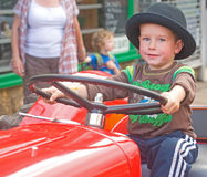 A young boy 'driving' a red tractor. Stock Photography