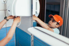 Young boy drying hands. Young boy wearing orange ball cap using commercial hand dryer in bathroom Royalty Free Stock Photography