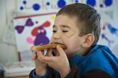 Young Boy Eating A Sandwich. Royalty Free Stock Image