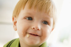 Young boy eating baby food with mess on face Stock Photo