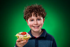 Young boy eating big sandwich. Young boy eating healthy sandwich on green background Royalty Free Stock Photos
