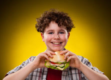 Young boy eating big sandwich. Young boy eating healthy sandwich on yellow background Stock Image