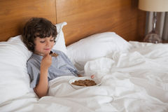 Young boy eating breakfast in bed Stock Photos