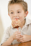 Young boy eating candy apple Stock Photo