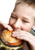 Young boy eating cheeseburger Stock Photo