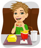Young boy eating cheeseburger with french fries and coke Stock Image