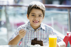 Young boy eating chocolate cake in cafe. Young boy eating piece of chocolate cake in cafe Royalty Free Stock Photo