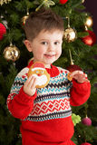 Young Boy Eating Cookie In Front Of Christmas Tree Stock Photo