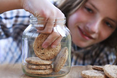 Young boy eating a cookie from the jar Royalty Free Stock Photos