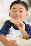 Young boy eating cookie in living room Stock Images