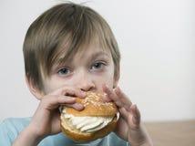 Young boy eating a cream bun Stock Photography