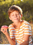 Young boy eating donut ourdoors. Teenager boy eating donut and licking lips outdoors at green background Royalty Free Stock Photography