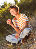 Young boy eating donut outdoors. Teenager boy holding donut and smiling outdoors at green background Stock Photography