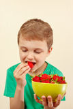 Young boy eating fresh ripe strawberries from bowl. Young boy eating fresh ripe strawberries from a bowl Royalty Free Stock Photos