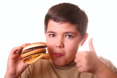 Young boy eating hamburger. On white Stock Photography