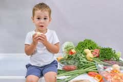 Young boy eating healthy meal seated at a table stock photo