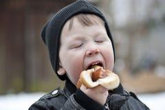 Young boy eating hotdog. Young boy eating a hotdog with ketchup outdoors Stock Photo