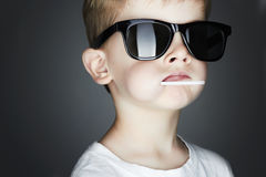 Young Boy Eating A Lollipop.child in sunglasses Stock Image