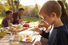 Young boy eating at a picnic table in a park Royalty Free Stock Photo
