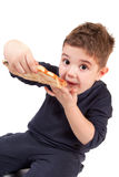 A young boy eating pizza Stock Photos