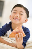 Young boy eating pizza slice in living room. Smiling Royalty Free Stock Photo