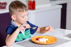 Young Boy Eating Plate of Cheese and Fruit Stock Image
