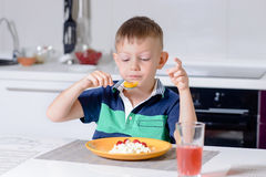 Young Boy Eating Plate of Cheese and Fruit Stock Photography