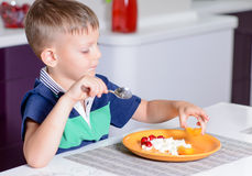 Young Boy Eating Plate of Cheese and Fruit Stock Photo