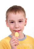 Young boy eating potato chips. Young Caucasian boy eating potato chips, on white background Stock Photos