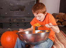 Young boy eating pumpkins Royalty Free Stock Images