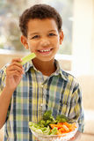 Young boy eating raw vegetables Royalty Free Stock Image