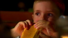 Young boy eating sandwich stock footage