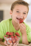 Young boy eating strawberries in living room. Smiling Royalty Free Stock Photography