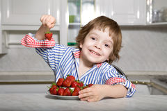 Young boy eating strawberry in kitchen. Young boy smiling taking strawberry from the plate in kitchen Stock Photos