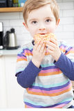 Young Boy Eating Sugary Donut For Snack Stock Photo
