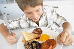 Young Boy Eating Unhealthy Fried Breakfast Royalty Free Stock Photo