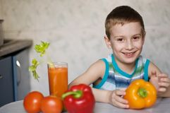 Young boy eating vegetables. Young smiling boy eating vegetables Royalty Free Stock Photography