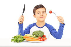 Young boy eating vegetables seated at table Stock Photos