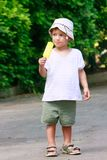 Young boy eating yellow ice-cream stock image