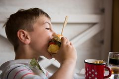 Young boy eats big hamburger. Little child consumes large sandwich and chips Stock Images