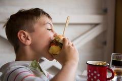 Young boy eats big hamburger Stock Images