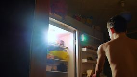 Young boy eats hunger and gluttony from the refrigerator at night. teen boy looks into the fridge at night. gluttony