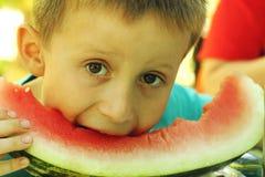 Young boy eats melon Royalty Free Stock Photos