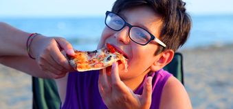 Young boy eats a slice of pizza on the beach at sunset in summer Stock Image