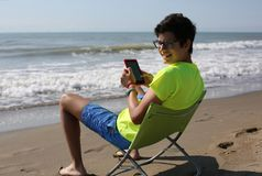 Young boy with ebook and shorts on the beach in summer. Smiling young boy with ebook and shorts on the beach in summer Royalty Free Stock Image